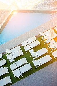 Sonnen-Stühle am Wasser